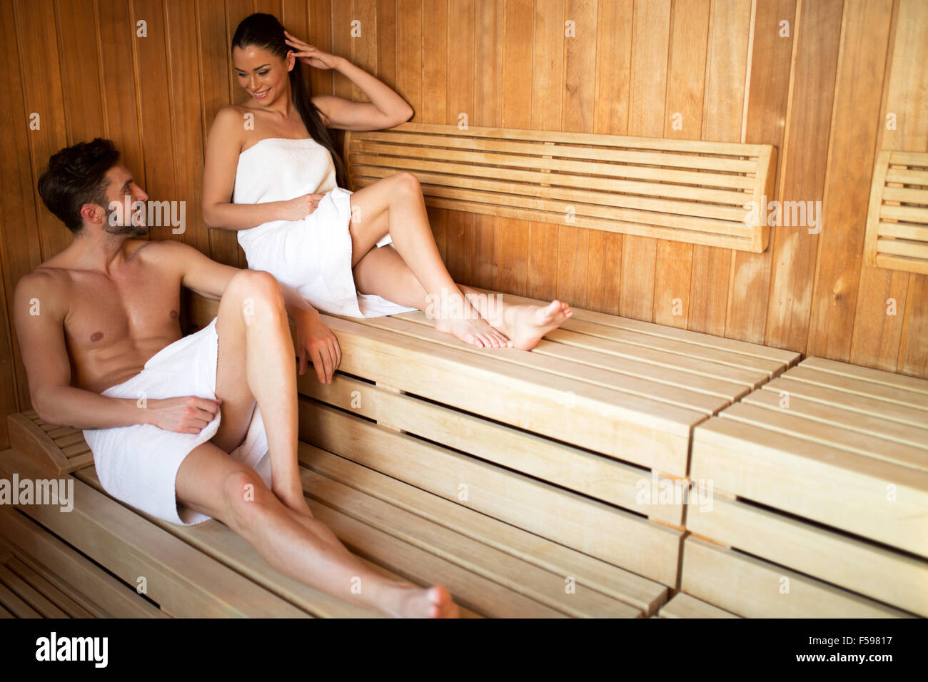 Jung und schön paar entspannende und Talkingin eine Sauna mit Handtuch vertuschen ihre Körper Stockbild