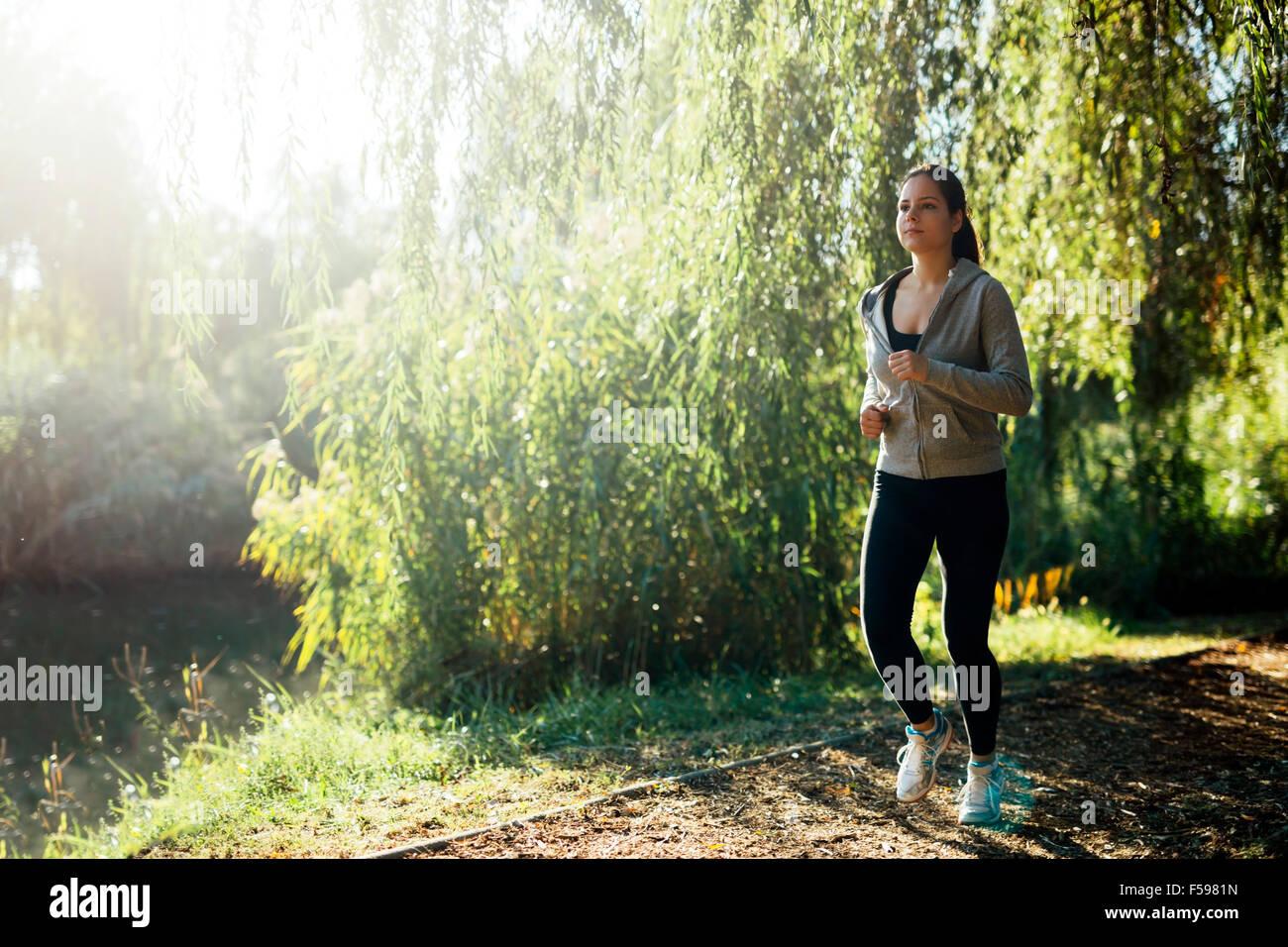 Sportliche Mädchen Joggen im Park in der Nähe eines Flusses Stockbild