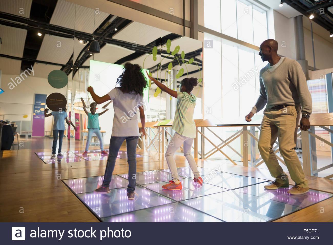 Vater beobachtete Töchter Tanz im Science center Stockbild