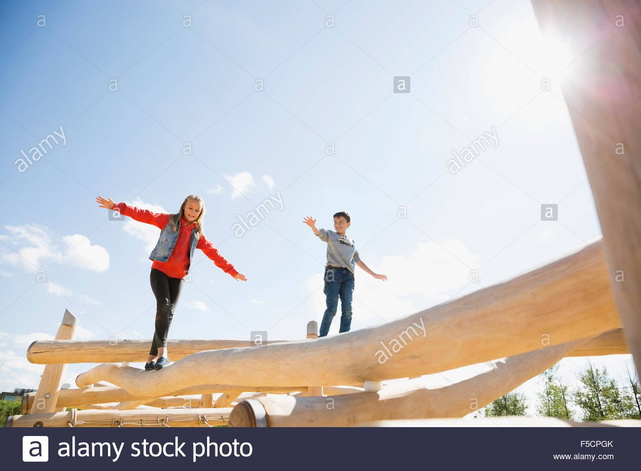 Jungen und Mädchen balancing Protokolle sonnige Spielplatz Stockbild
