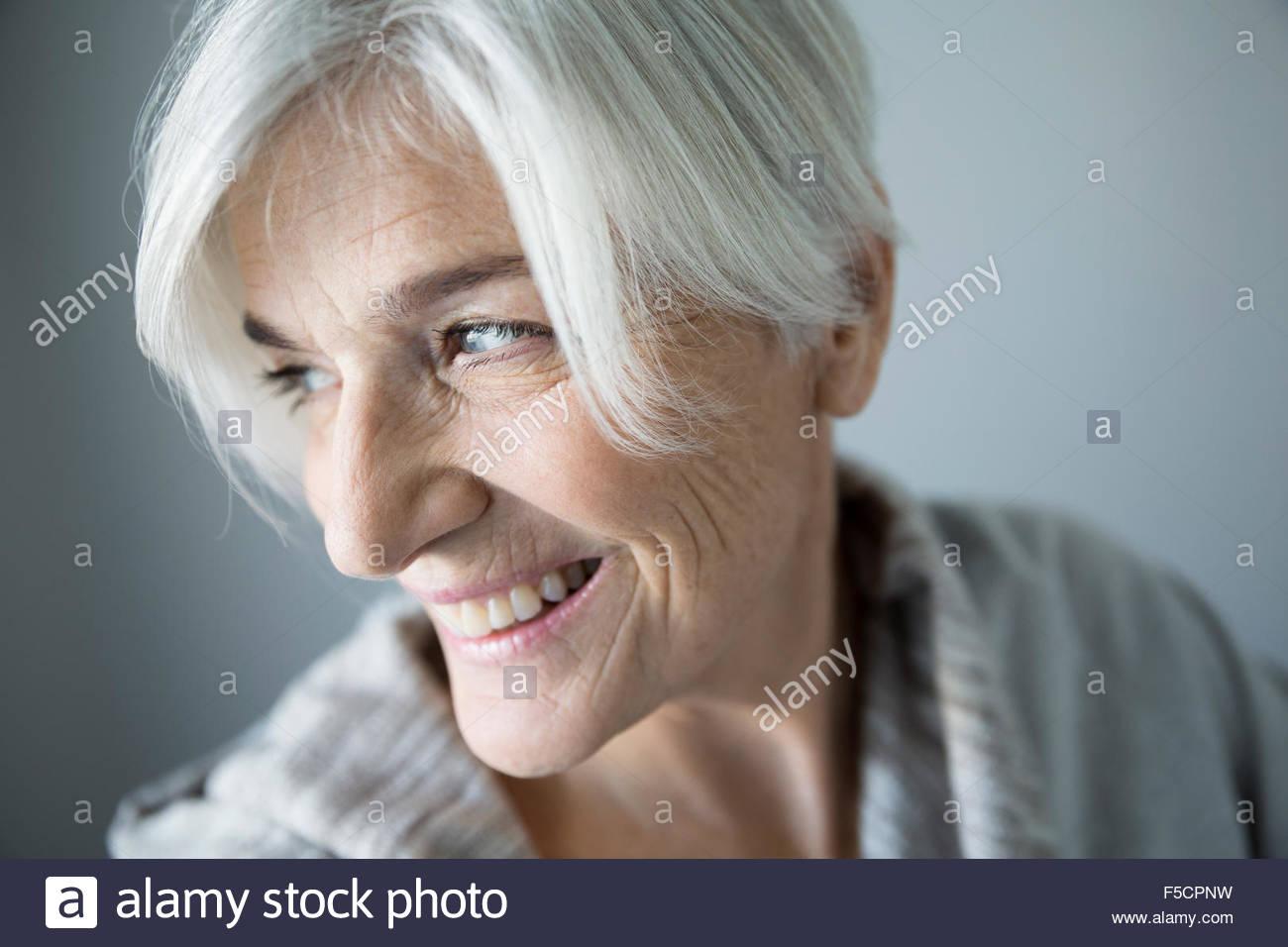 Nahaufnahme der lächelnde ältere Frau über die Schulter schauen Stockbild