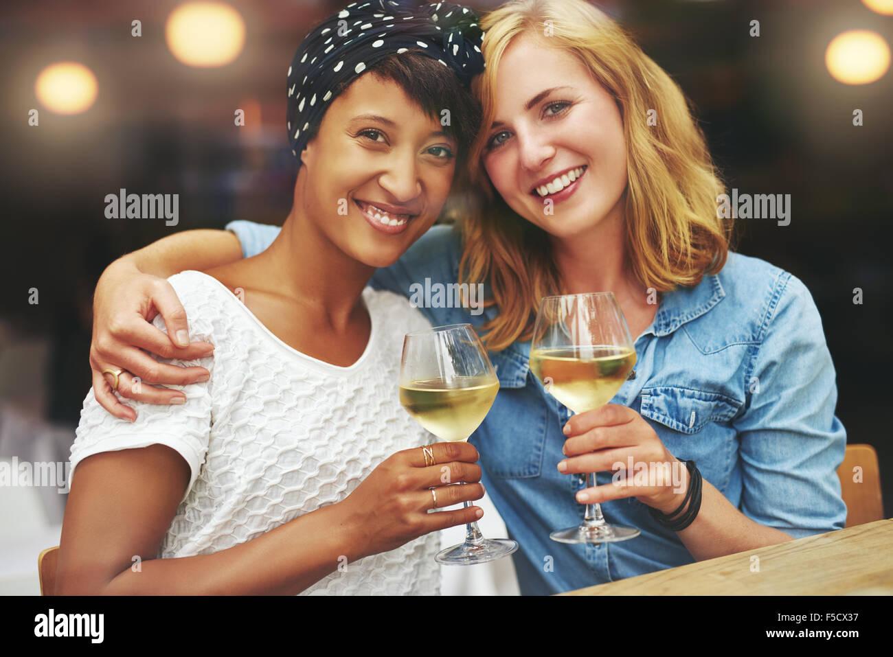 Zwei wunderschöne junge Multiethnischen Frauen bei einem Glas Wein ihre Gläser in einen Toast auf die Stockbild