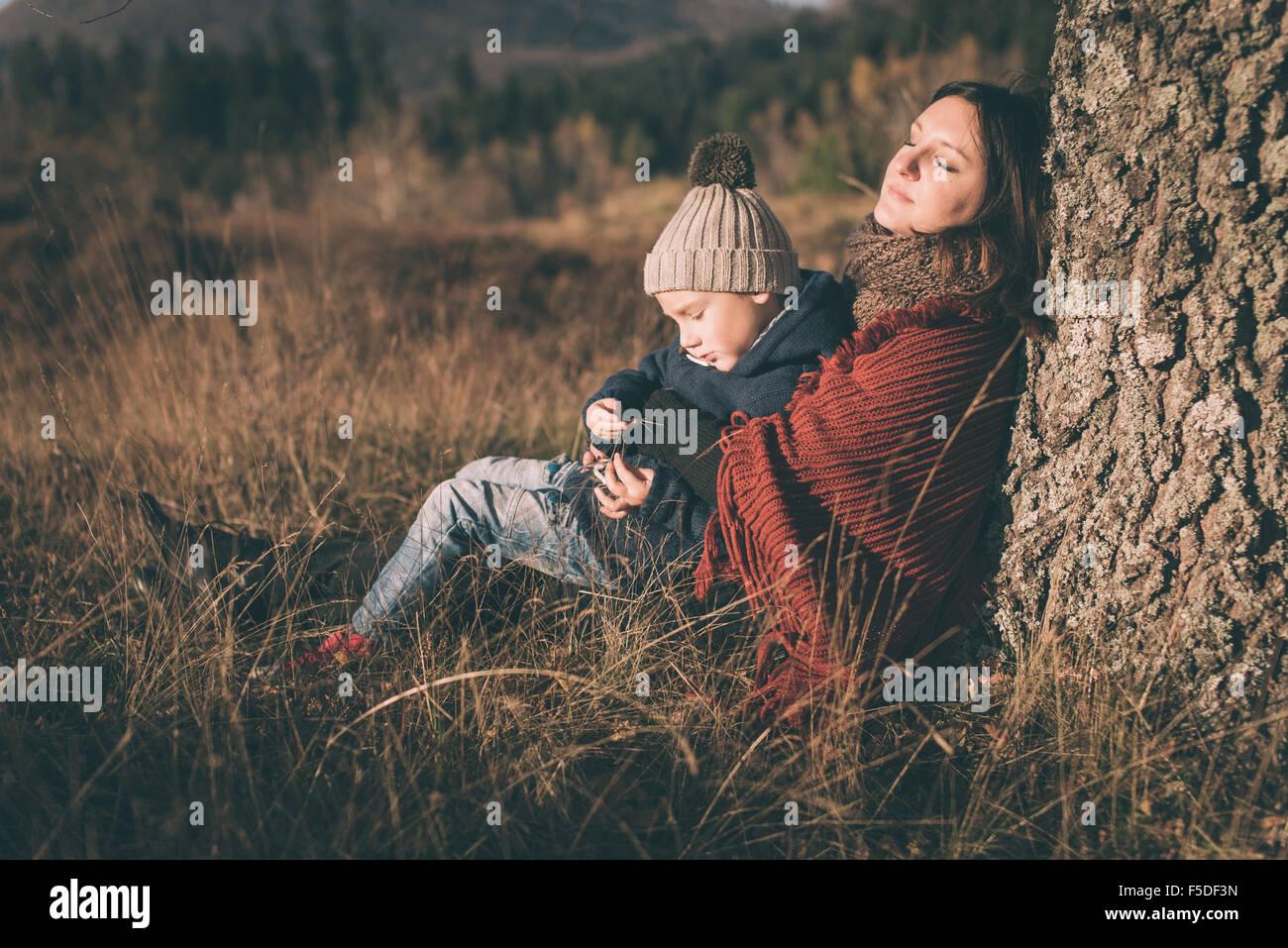 Mutter und Sohn unter dem Baum sitzt. Stockbild