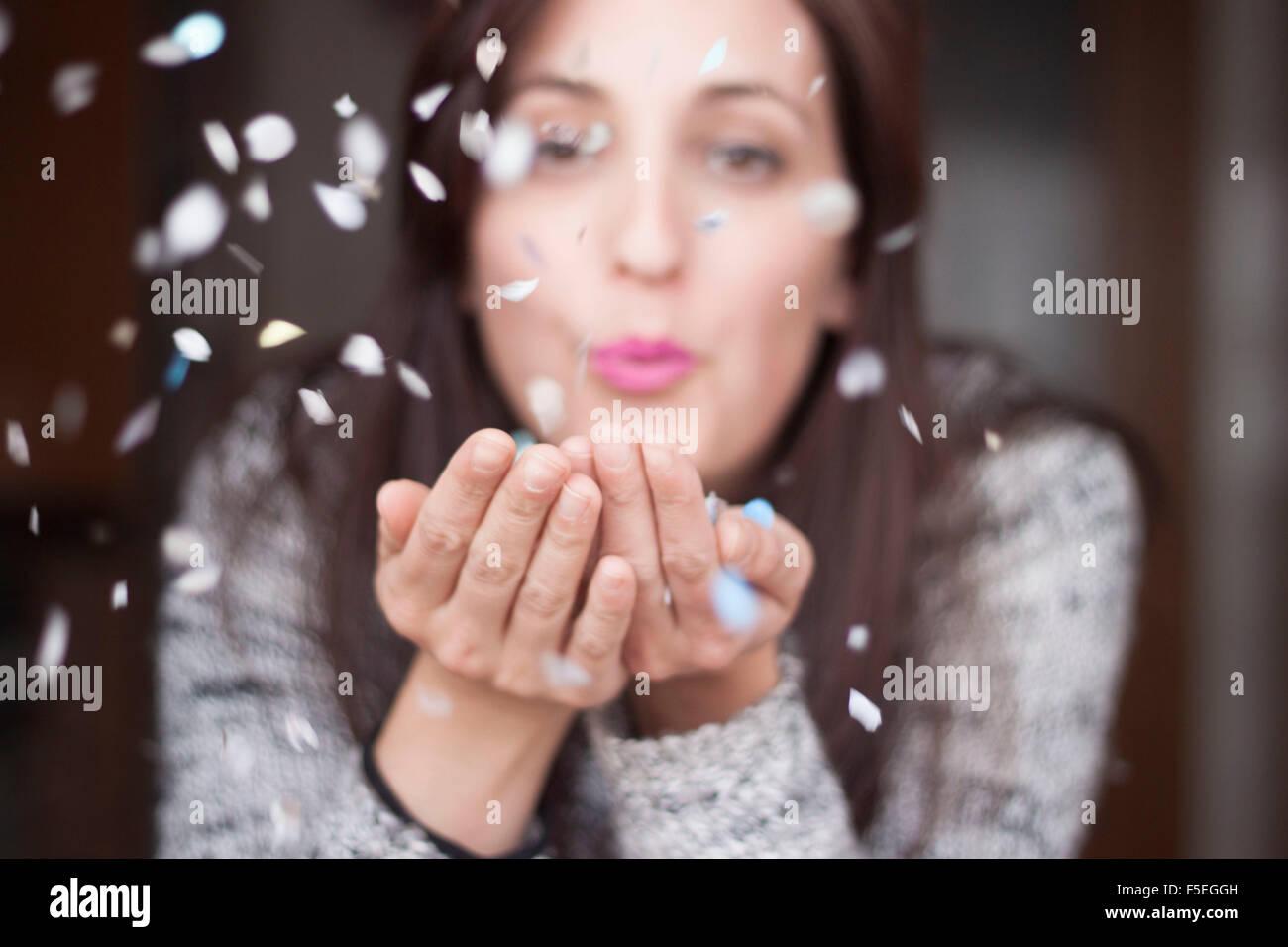 Frau bläst Konfetti in ihren Händen Stockbild