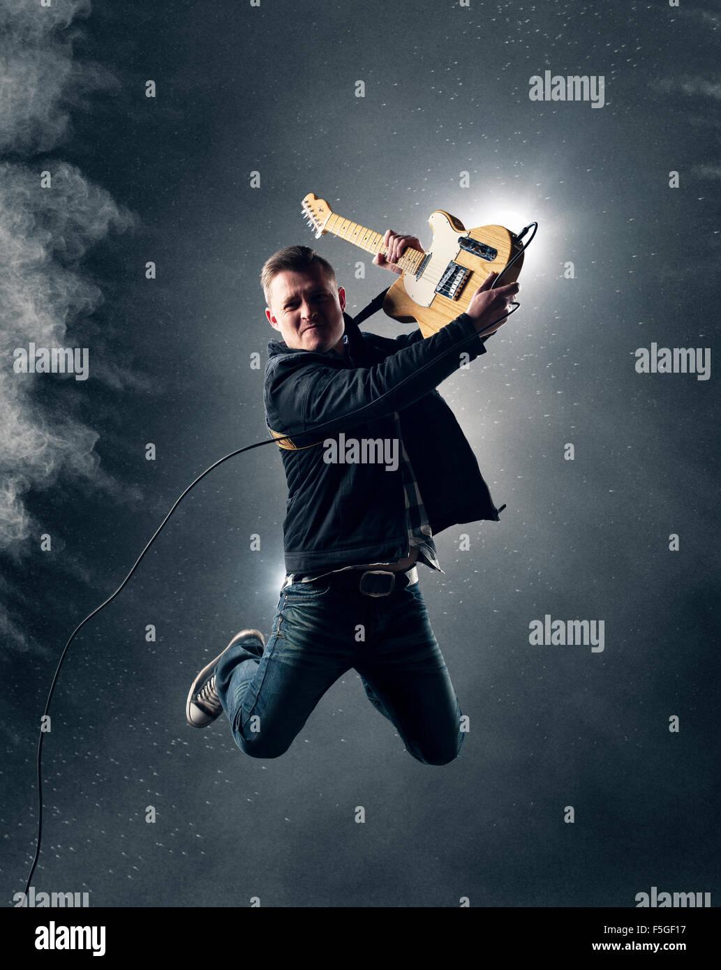 Rock und Roll-Gitarrist springt mit e-Gitarre mit Rauch und Pulver im Hintergrund Stockbild