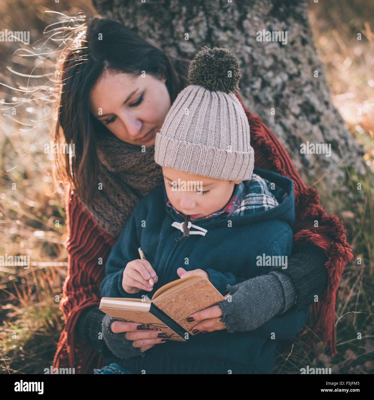 Mutter hilft ihrem Sohn erste Briefe schreiben Stockbild