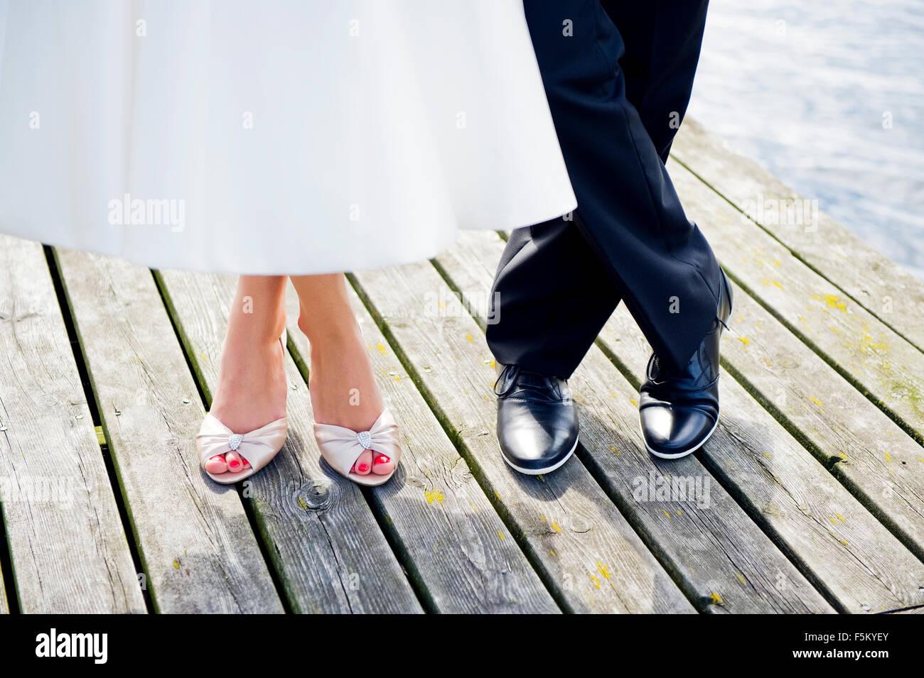 Füße von Mann und Frau stehen auf hölzernen Pier, Arholma, Uppland, Schweden Stockbild