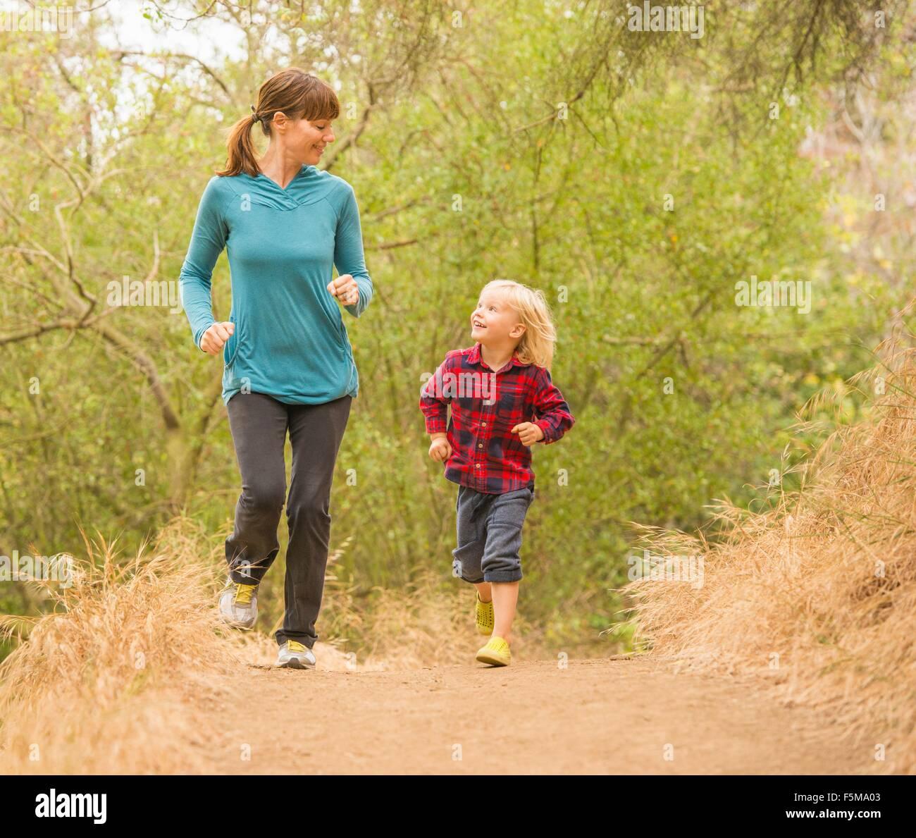 Mutter und Sohn läuft im Wald Stockbild