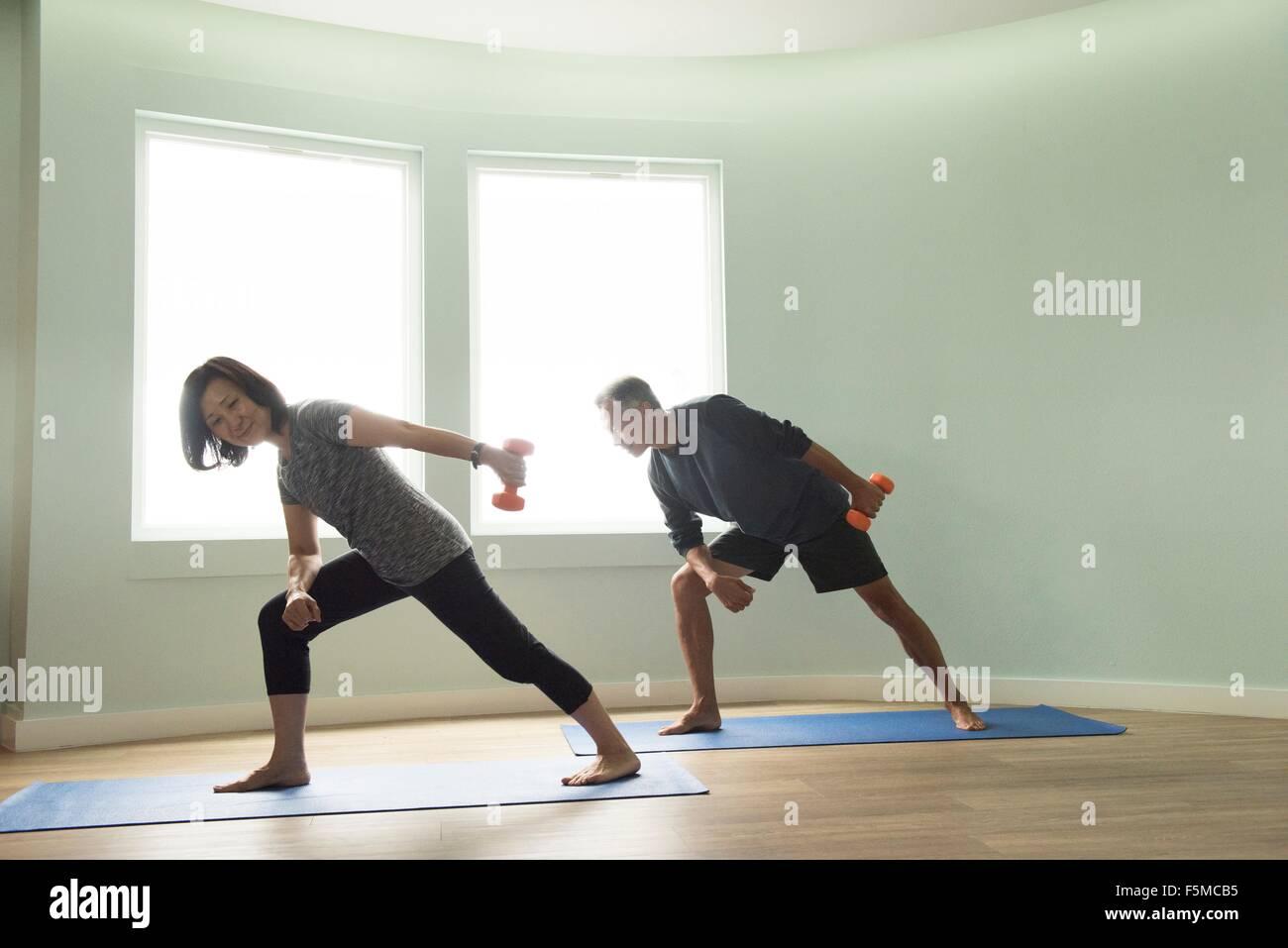 Älteres Paar auf Yoga-Matten-Training mit Hanteln Stockbild