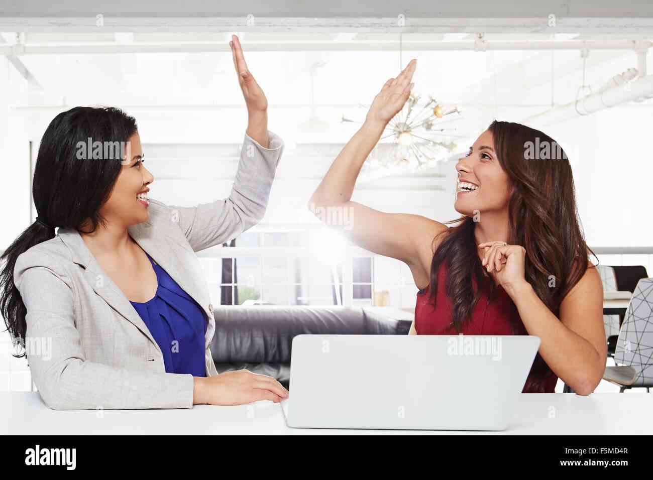 Zwei Geschäftsfrauen sitzen am Schreibtisch, geben hohe fünf Stockbild