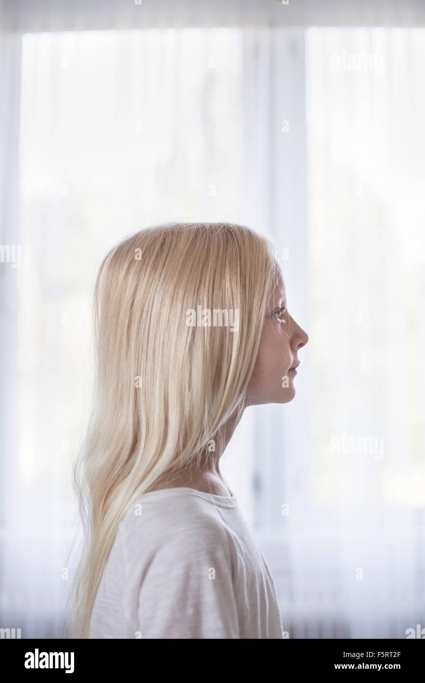 Schweden, Seitenansicht von blonden Mädchen (10-11) vor weißen Vorhängen Stockbild