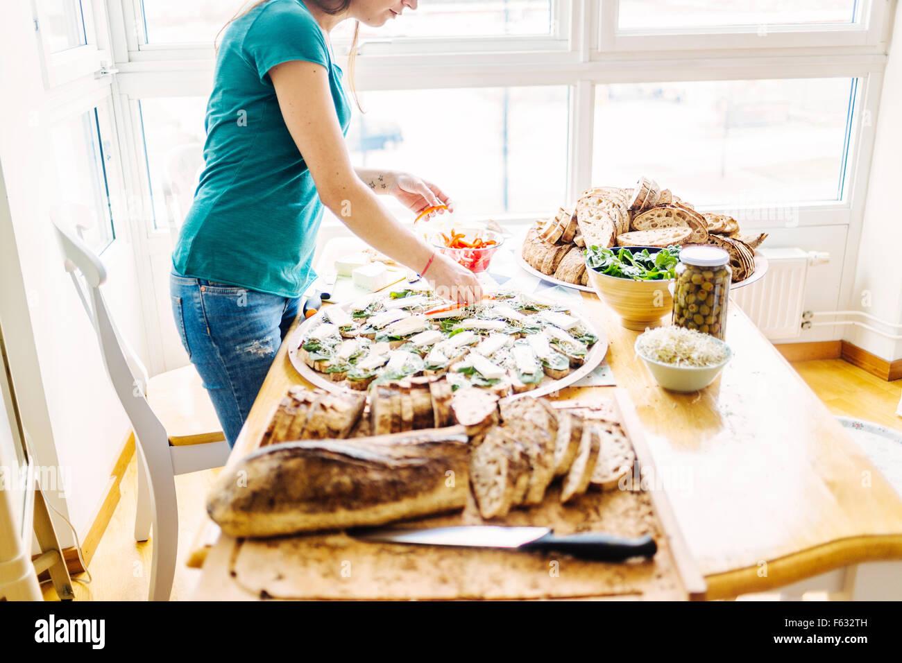 Seitenansicht der Frau bereitet angesichts offener Sandwich am Tisch Stockbild