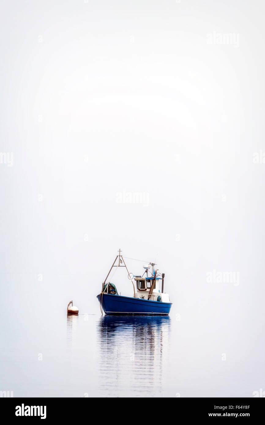 ein Fischerboot auf einem nebligen Meer Stockbild