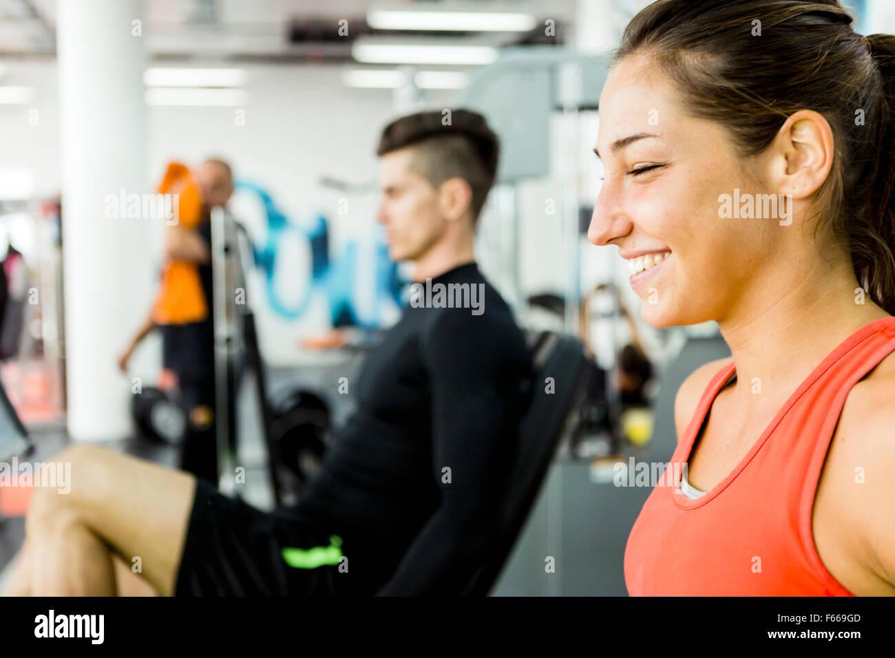 Ein gut aussehender Mann und eine schöne Frau, die gemeinsam in einem Fitness-Studio und Verklebung Stockbild