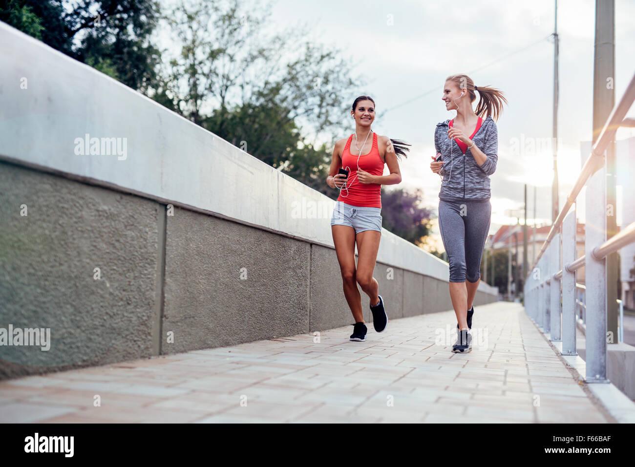 Schöne Landschaft von zwei weiblichen Jogger verfolgt ihre Aktivitäten im Freien in der Stadt in der Dämmerung Stockbild