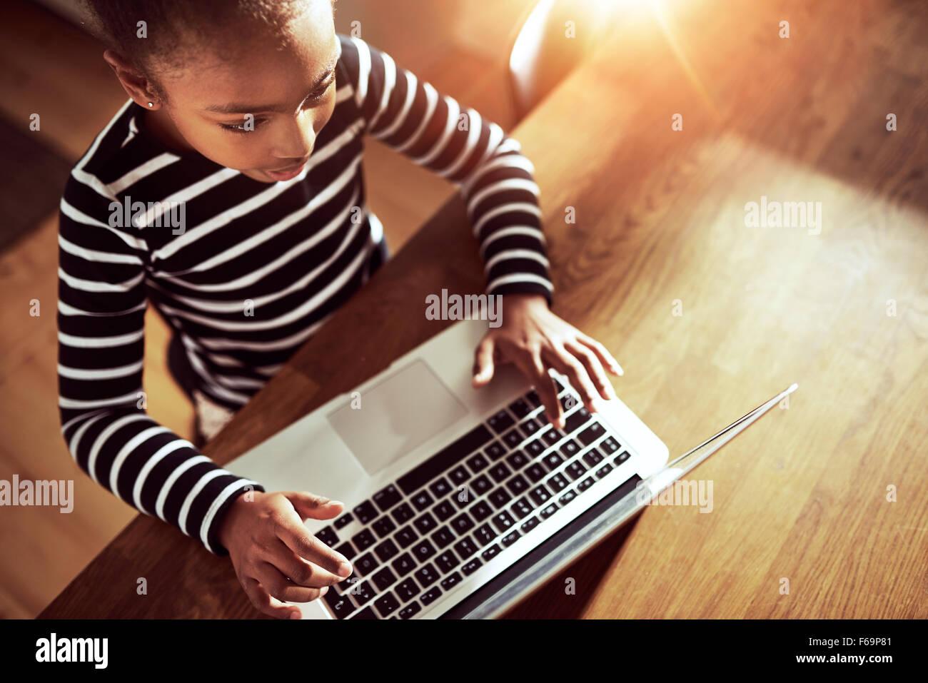 Junge ethnische schwarze Mädchen sitzen am Esstisch zu Hause Texteingabe auf einem Laptop, hohe Betrachtungswinkel Stockbild