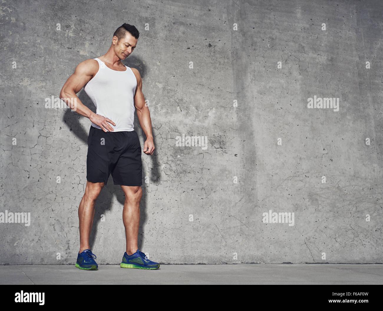 Männliche fitness Modell in Weiß tank top Entspannung nach dem Training. grauer Hintergrund mit Raum für Stockbild