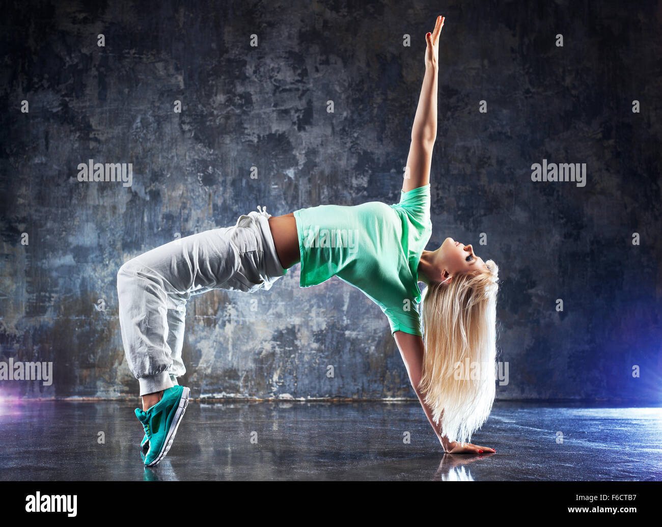 Moderne junge Frau Tänzerin. Auf dunklen Stein Wand Hintergrund. Stockbild