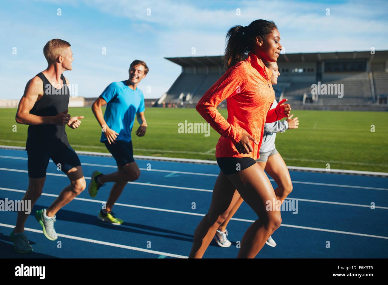 Passen Sie Männer und Frauen, die auf einer Rennstrecke. Gemischtrassig Sportler üben auf Rennen verfolgen Stockbild