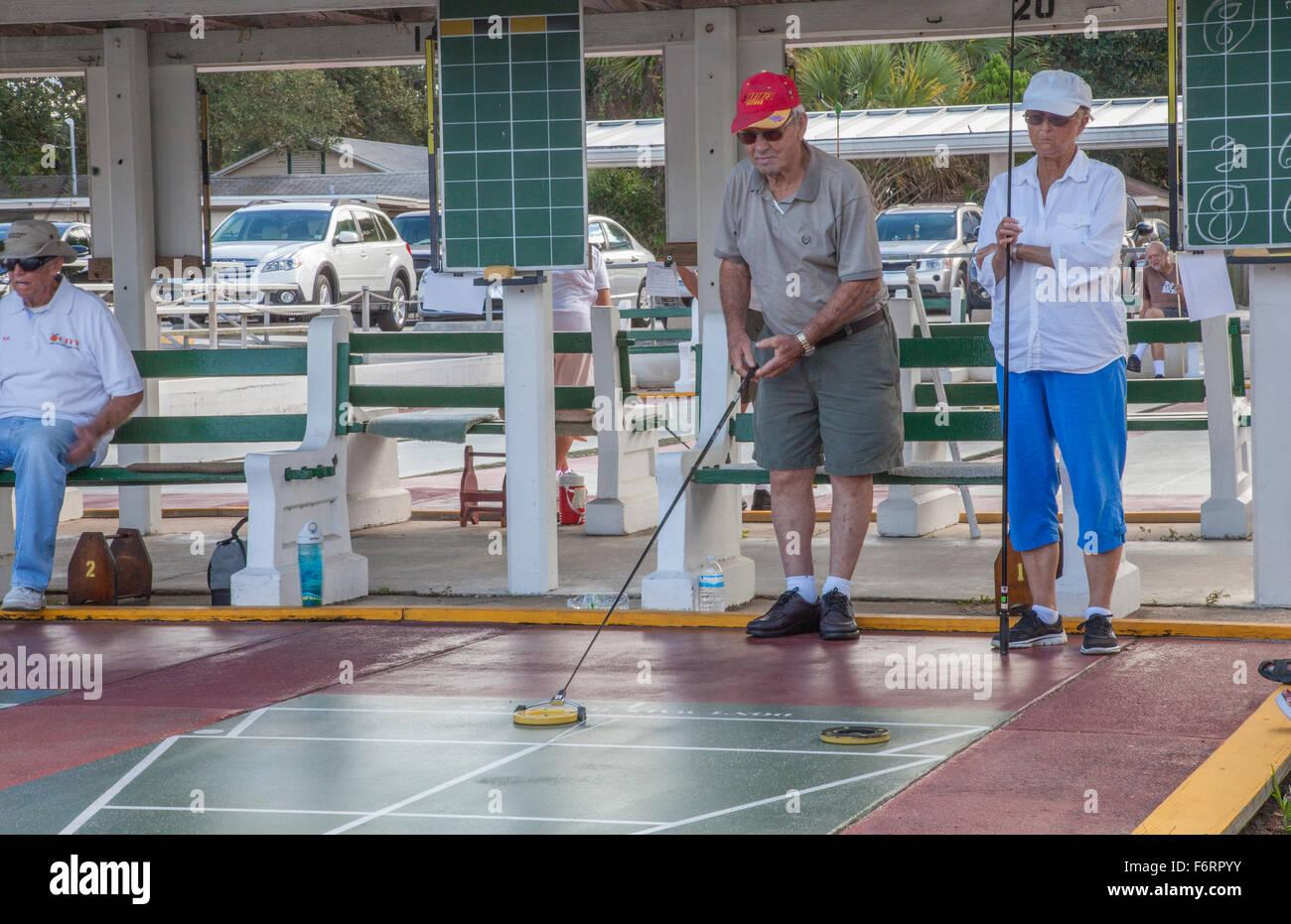 Senioren, die wettbewerbsfähige Shuffleboard Spiel in Flager Ave in New Smyrna Beach, Florida Stockbild