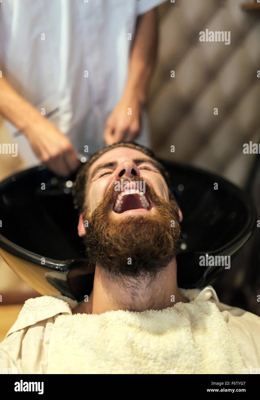 Barber waschen Haare eines Kunden mit offenem Mund Stockbild