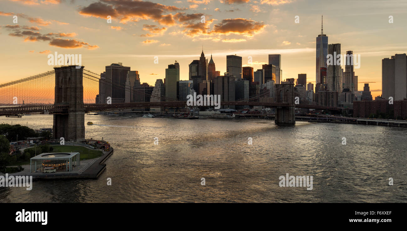 Lower Manhattan Wolkenkratzer und Financial District Skyline bei Sonnenuntergang mit der Brooklyn Bridge über Stockbild