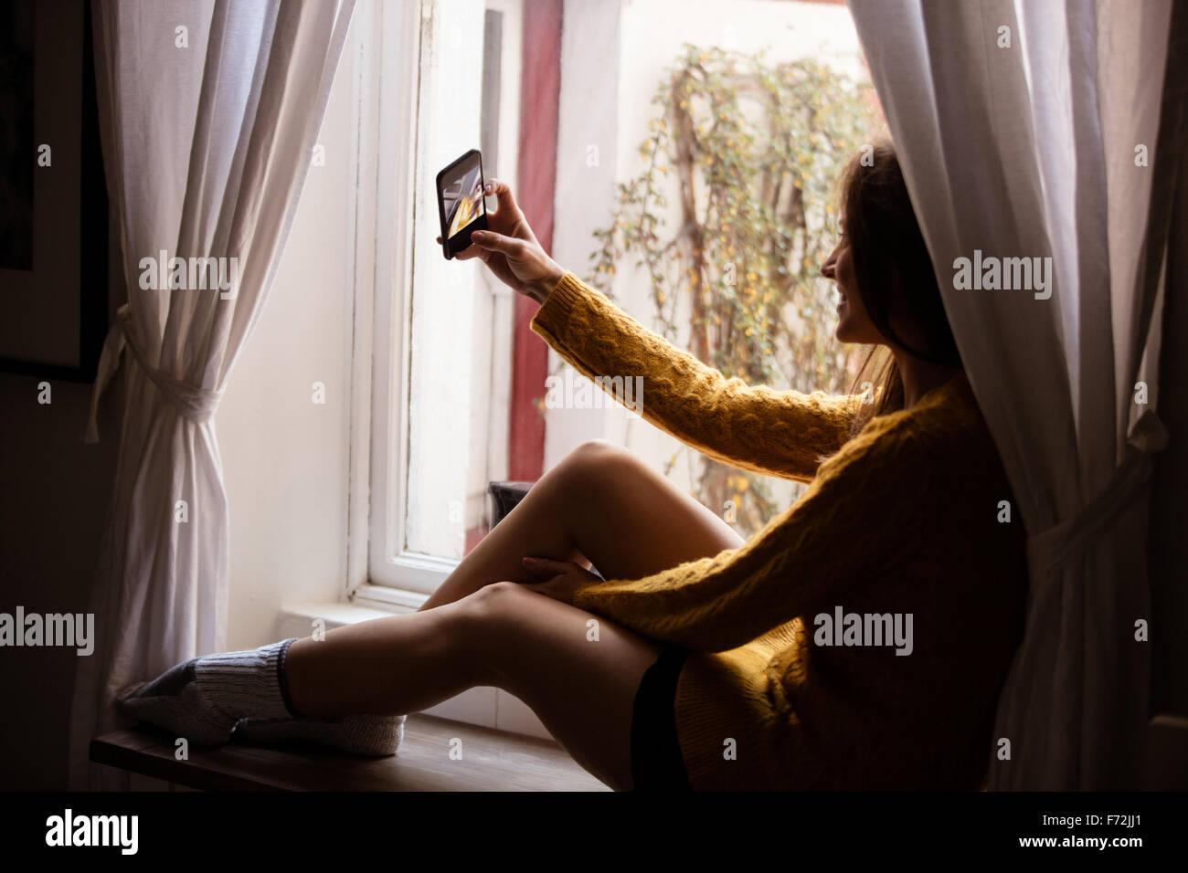 Junge Frau, die eine Selfie am Fenster Stockfoto