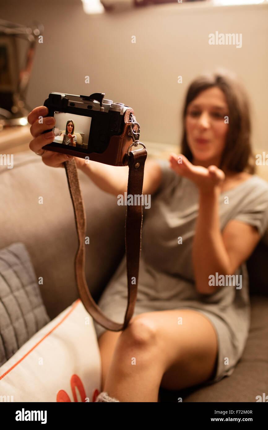 Glückliche Frau nehmen Selfie mit Kamera Stockbild