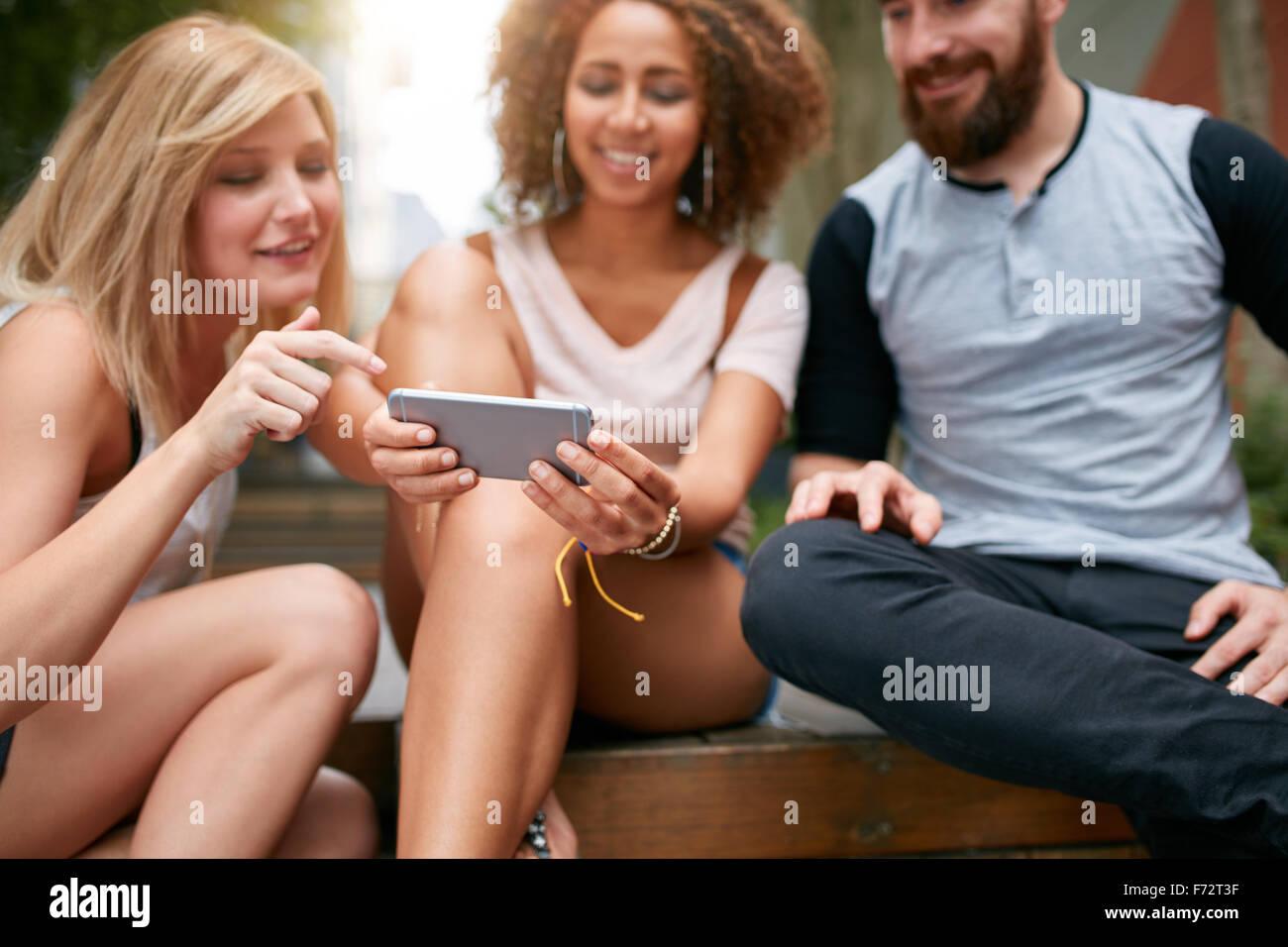 Schuss von jungen Erwachsenen, die auf der Suche etwas Interessantes auf Handy hautnah. Junge Freunde mit Handy Stockbild