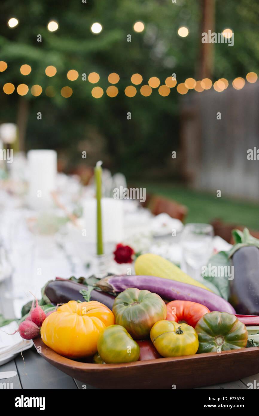 Langer Tisch set mit Teller und Gläser, Essen und trinken in einen Garten, eine Schüssel mit Gemüse Stockbild