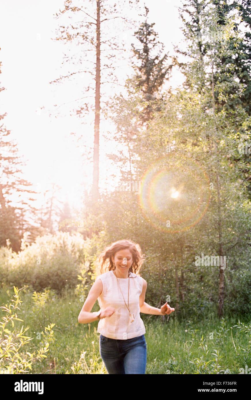 Lächelnde Frau läuft durch einen sonnendurchfluteten Wald. Stockbild