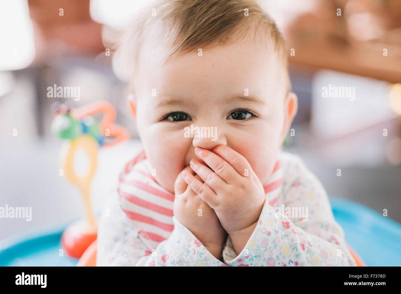 Ein kleines Mädchen mit ihren Händen über den Mund in die Kamera schaut. Stockbild