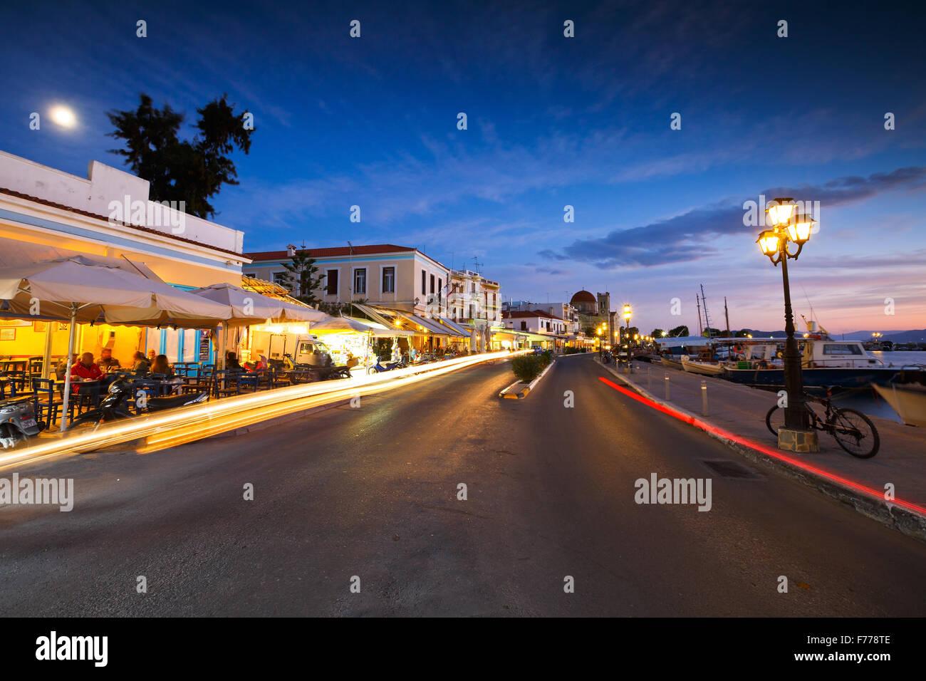 Blick auf die Promenade mit Cafés, Bars und Restaurants und Angelboote/Fischerboote im Hafen von Aegina Insel, Stockbild