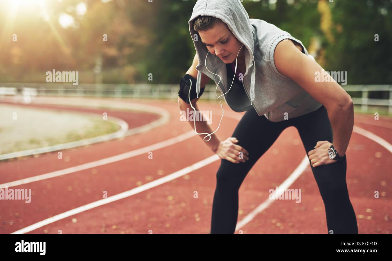 Junge Sportlerin auf Stadium und Musik hören, nach unten schauen. Stockbild