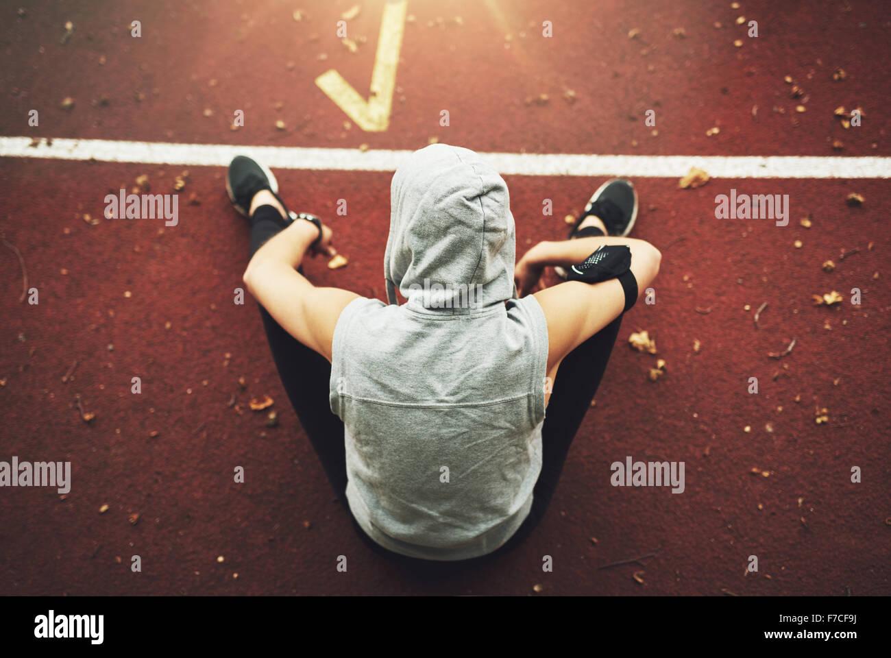 """Rückansicht der junge Frau in Sportkleidung sitzen auf """"Track"""" und die Vorbereitung vor dem Training. Stockbild"""