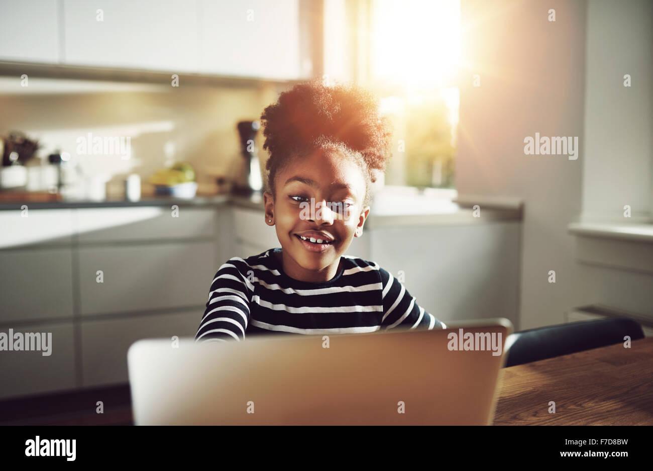 Nette junge schwarze Mädchen spielen auf einem Laptop Computer glücklich lächelnd, während Sie Stockbild