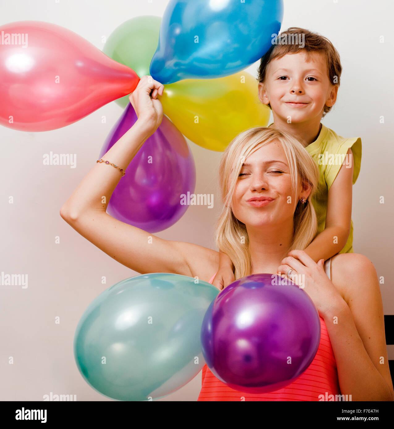 ziemlich real Familie mit Luftballons Farbe auf weißem Hintergrund, blonden Frau mit kleinen Jungen Geburtstagsparty Stockbild