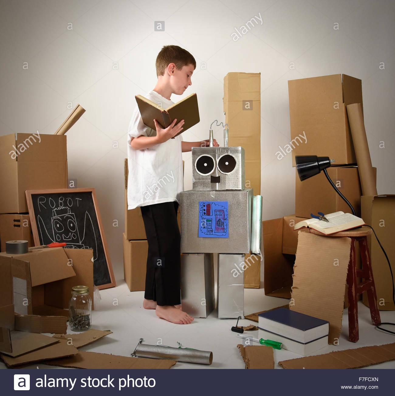 Ein Kind ist ein Buch zu lesen und bauen einen Roboter aus Pappkartons für eine Fantasie, Wissenschaft und Stockbild