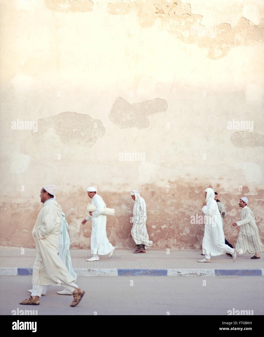 Marokkanische muslimische Männer gehen zügig vorbei an der Stadtmauer auf dem Weg zum Morgengebet. Essaouira, Stockbild