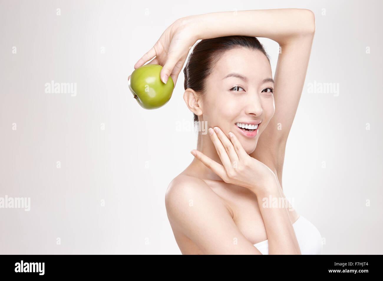 Eine lächelnde Frau hält einen grünen Apfel Stockbild
