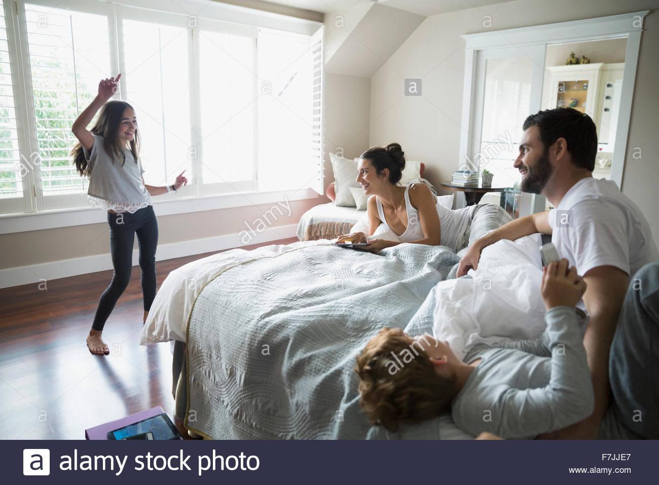 Familie beobachten Mädchen tanzen im Schlafzimmer Stockbild
