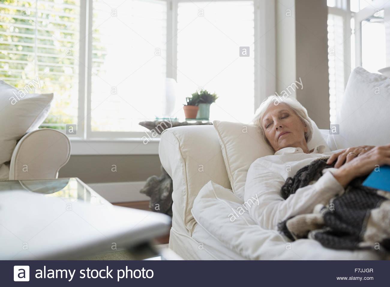 Müde senior Frau Nickerchen auf dem Sofa im Wohnzimmer Stockbild