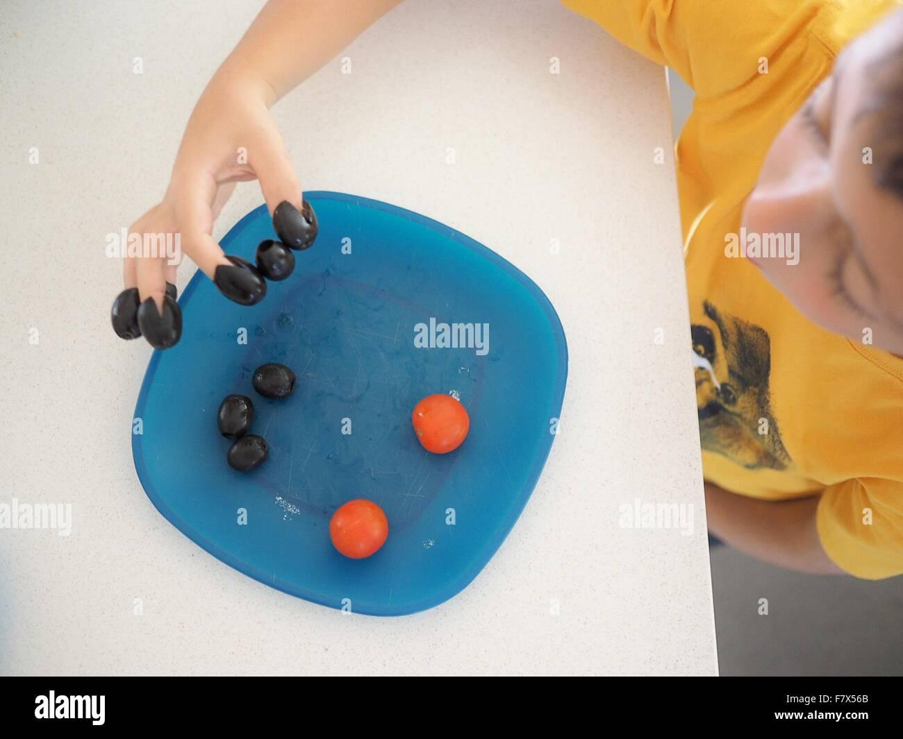 Junge mit seinem Essen, Oliven auf seine Finger spielen Stockbild