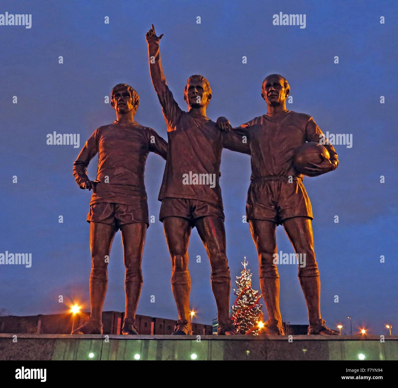 Laden Sie dieses Alamy Stockfoto Vereinigte Trinity/Heilige Dreifaltigkeit Statue von Manchester United Trio von Bobby Charlton, George Best und Denis Law in der Abenddämmerung - F7YN94