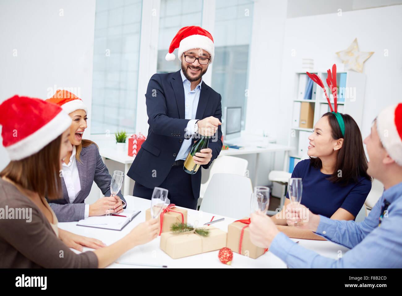 Gruppe von Mitarbeitern betrachten ihre Kollegin Eröffnung Flasche Champagner Stockbild