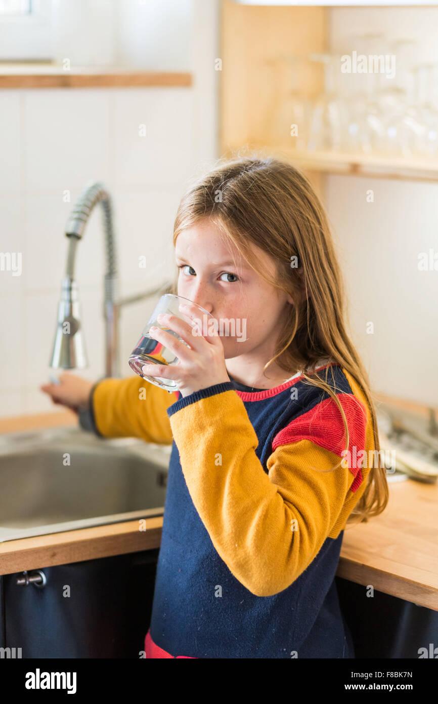 9 Jahre altes Mädchen trinken Wasser aus dem Wasserhahn. Stockbild