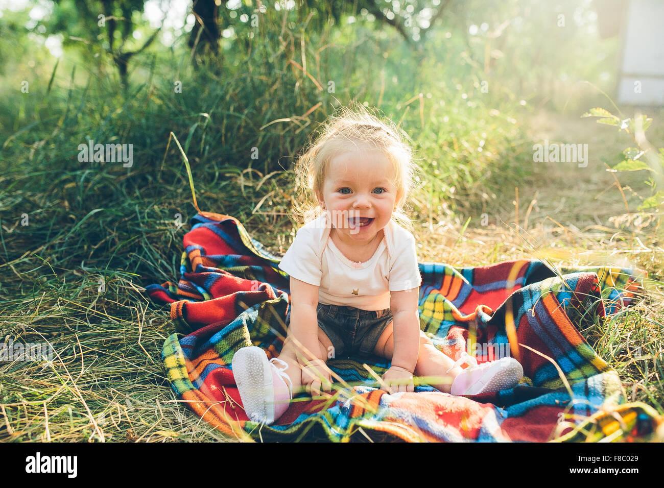 kleines Mädchen sitzen auf dem Rasen Stockbild