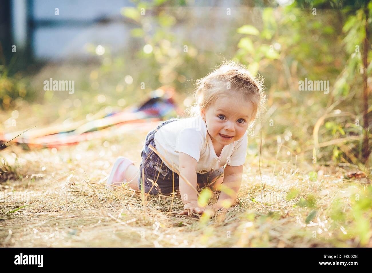 kleines Mädchen auf dem Rasen krabbeln Stockbild