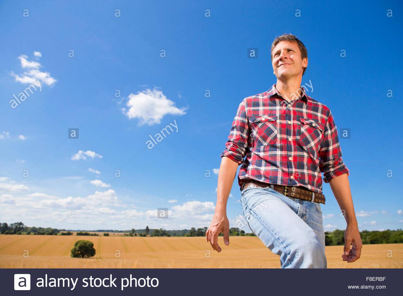 Lächelnde Bauern Wandern in sonnigen ländlichen Gerstenfeld Ernte im Sommer Stockbild