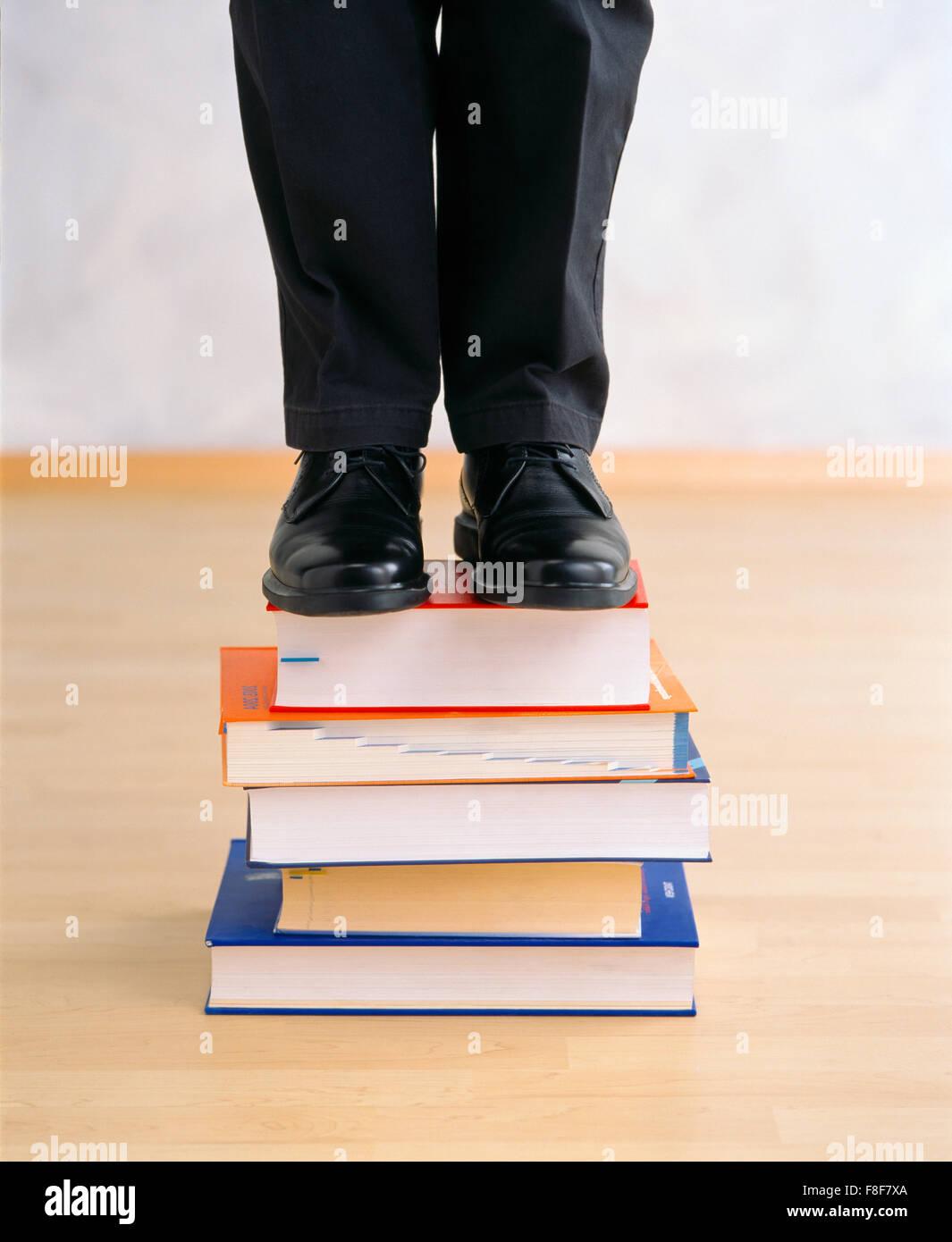 Mann auf einem bookpile Stockbild